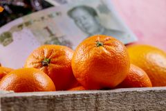 Chinese new year tangerine oranges on wooden table top. Chinese yuan bank-notes royalty free stock images
