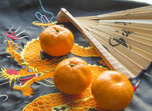 Chinese New year, tangerines and a fan lying on the silk fabric with an embroidered dragon royalty free stock images