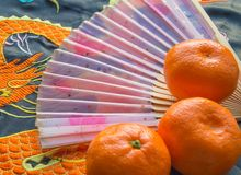 Chinese new year-traditional pink fan and tangerines on silk fabric, background with embroidered dragon stock images
