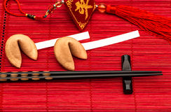 Chinese new years lucky charm, fortune cookies and black chopsti. Cks on red bamboo mat Stock Photography