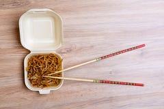 Chinese noedels in doos met eetstokjes op houten royalty-vrije stock foto