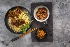 Chinese noodles with grilled meat, vegetables and greens on a gray table. stock photos