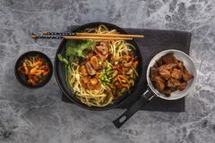 Chinese noodles with mushrooms, fried meat in a pan, vegetables and herbs are on the gray table. stock photos