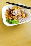 Chinese noodles street fare. A photograph showing a dish of chinese flat yellow noodles served with minced pork, meat slices and china mushrooms, garnished with Stock Photos