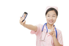 Asian nurse using a cell photo to take a Selfie isolated on white background. Beautiful Asian nurse using a cell photo to take a Selfie of herself isolated on a royalty free stock images