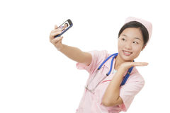 Asian nurse using a cell photo to take a Selfie isolated on white background. Beautiful Asian nurse using a cell photo to take a Selfie of herself isolated on a royalty free stock image