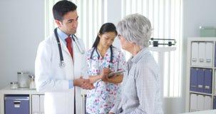 Chinese nurse weighing elderly patient Stock Photos