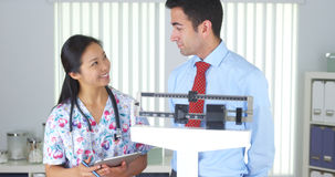 Chinese nurse weighing Mexican patient Royalty Free Stock Image