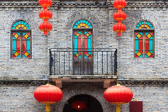 Chinese old style building facade. Detail of Chinese old style building facade with colorful windows and hanging lanterns as an ornament.This is architectural Royalty Free Stock Photos