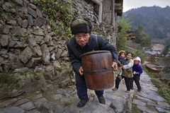 Chinese older man climbs stone mountain road with wooden barrel Royalty Free Stock Photos