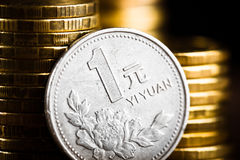 Chinese One Yuan Coin  and gold money. On the desk. Peony flower depicted in the Chinese one Yuan coin Royalty Free Stock Photo