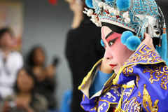 Chinese Opera Actor getting ready for a show. A picture showing a Chinese Opera Actor fixing her costume, preparing for a show Stock Image