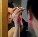 A chinese opera actor is painting his face Royalty Free Stock Image