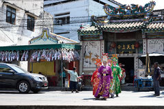 Chinese opera actors walking across the street to offering Shrine of the Black Sea Stock Photo