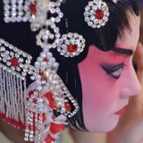 A chinese opera actress is painting her face Royalty Free Stock Photo