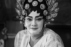 A Chinese opera actress painting mask on her face before the performance at backstage at major shrine in Bangkok's chinatown on Oc Stock Images
