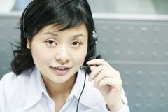 Chinese operator with headset. Attending a phone call Stock Images