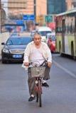 Chinese oudste op zijn fiets in bezig verkeer, Peking, China Royalty-vrije Stock Fotografie