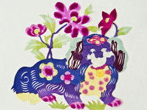 Chinese paper cutting dog. A color Chinese paper cutting dog with some flowers Royalty Free Stock Photos