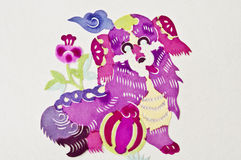 Chinese paper cutting dog. A color Chinese paper cutting dog with some flowers Stock Photos