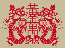 Chinese paper-cutting twins dragons with a Chinese charm inscription Royalty Free Stock Image