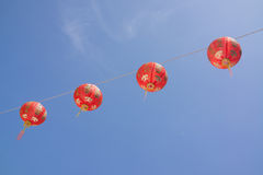 Chinese paper lanterns hanging on the rope. Row of Chinese paper lantern hanging on the rop with blue sky in the background Stock Photos