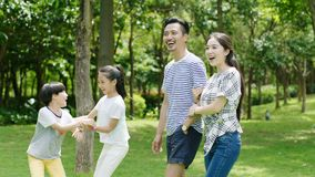 Asian family enjoying family time in park in summer. Chinese parents and kids enjoying family time in park in summer Royalty Free Stock Photo