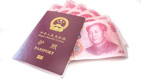 Chinese passport with some 100 Chinese yuan cash. Chinese passport and Chinese currency 100 yuan notes with Chairman Mao`s portrait on a white background Royalty Free Stock Image