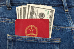 Chinese passport and dollar bills in the jeans pocket Royalty Free Stock Photo
