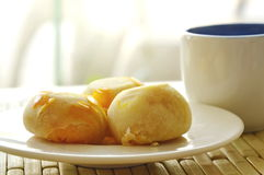 Chinese pastry stuffed mashed bean and salty egg yolk with tea cup. Chinese pastry stuffed mashed bean and salty egg yolk on dish with tea cup Stock Image