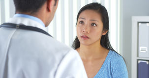Chinese patient talking to doctor about neck pain Stock Photography