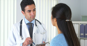 Chinese patient talking to hispanic doctor Stock Image