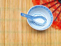 Chinese style background. Chinese patterned porcelain soup plate with spoon, on a bamboo placemat. Red lacy fan in the background. Empty space for the text royalty free stock image