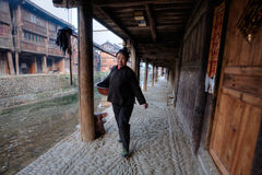 Chinese peasant woman walks along the river under wooden canopy. Stock Photography