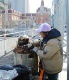 Chinese vendor selling  roasted sweet potato. A Chinese vendor  selling  roasted sweet potato on  bridge  Haihe river Tianjin China photoed on january 20th 2014 Stock Image