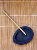 Chinese pen brush on ink stone. Writing instruments for an ancient type chinese calligraphy - painting brush, placed on a black stone slab for grinding ink. Used royalty free stock image