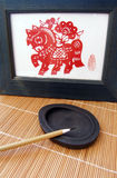 Chinese pen brush on ink stone. An ancient type chinese calligraphy, drawing or painting brush, placed on a black stone slab for grinding ink.  Used in chinese Royalty Free Stock Image