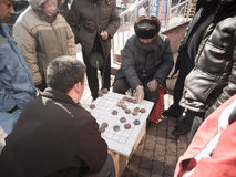 Chinese people play Xiangqi (Chinese Chess) at street side. Stock Photos
