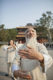 Chinese People Practicing Tai Ji in Front of Traditional Chinese Building Stock Image