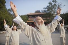 Chinese People Practicing Tai Ji in Front of Traditional Chinese Building Stock Photos