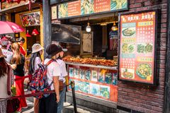 Chinese people queuing for meat skewers street food in Hubu Alley in Wuhan Hubei China stock image