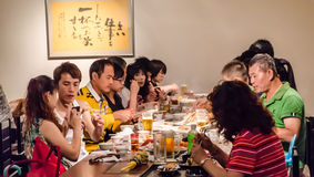 Chinese people in restaurant. Sapporo, Japan - July 7, 2014 : Group of Chinese tourist eat their food in Japanese tradition restaurant stock photos