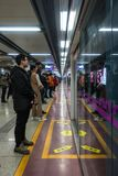 Chinese People Standing Waiting for Subway Behind Glass Reflecti royalty free stock photography