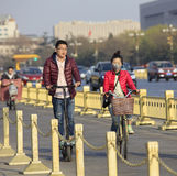 Chinese people transportation means. BEIJING, CHINA - MARCH 20, 2016: A woman rides a bicycle, man rides a electric scooter near Tiananmen square. Beijing royalty free stock photos