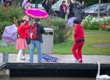 Chinese people with umbrellas visiting the UK and wearing bright clothes royalty free stock photography