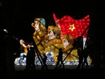 Chinese people walking in front of an illuminated communism sign