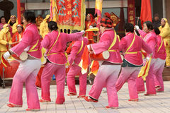 Chinese play drum and beat gong. Some Chinese with pink clothes  get together to play drums  and  dance to celebrate the lantern festival ,a boy sit on the Stock Image