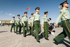 Chinese policemen on Tienanmen square. Group pf chinese policemen walking by rows of two on Tienanmen square in Beijing, China Royalty Free Stock Images