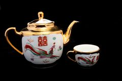 Chinese porcelain. Chinese fine traditional porcelain tea-kettle and cup on black background Royalty Free Stock Images