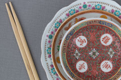Chinese porcelain. Closeup of three Chinese porcelain plates and chopsticks top view in studio shot Royalty Free Stock Photography